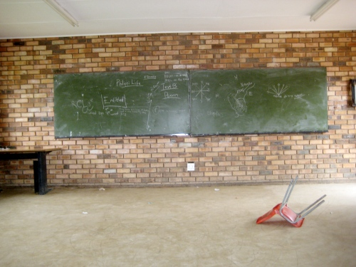 Disheveled Grade 7 classroom in Soshanguve.  Overturned chairs are violently chaotic, no?